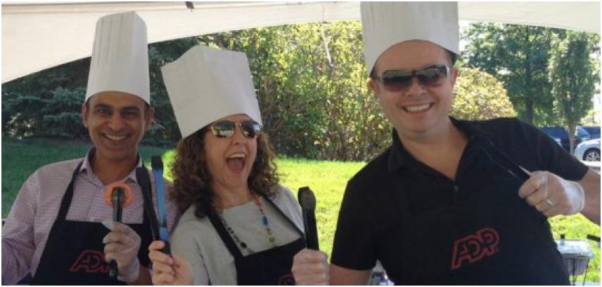 trois associés d'ADP portant des chapeaux de chef et tenant des ustensiles de barbecue