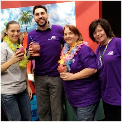 ADP s'associe en t-shirts violets avec certains portant des leis hawaïens et tenant des boissons tropicales