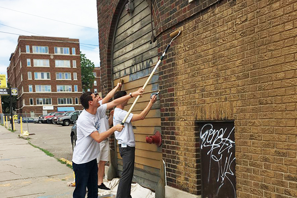 three Ecolab interns clean graffiti from city a building