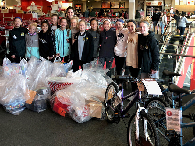 Amy G. posing with her youth soccer team and their Giving Season gift purchases