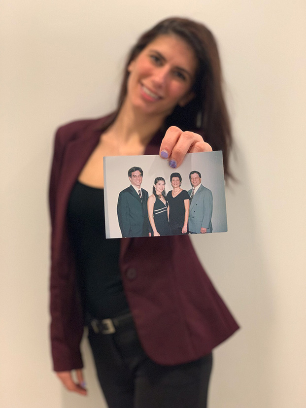 Kristen (blurred in background) holding a photo of her family (in foreground)