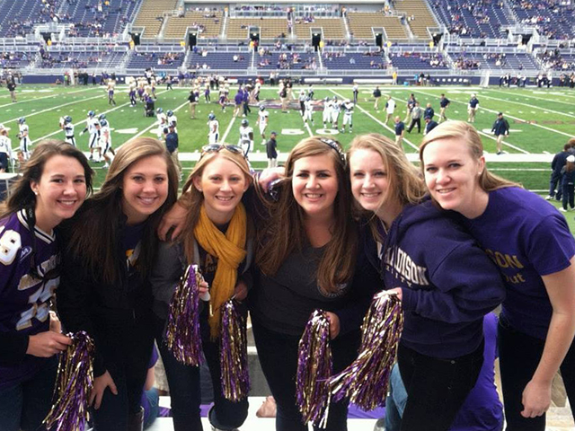 Emily A poses with her college roommates at a football game