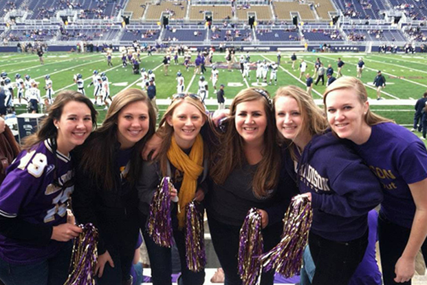 Emily A. poses with college roommates at a football game