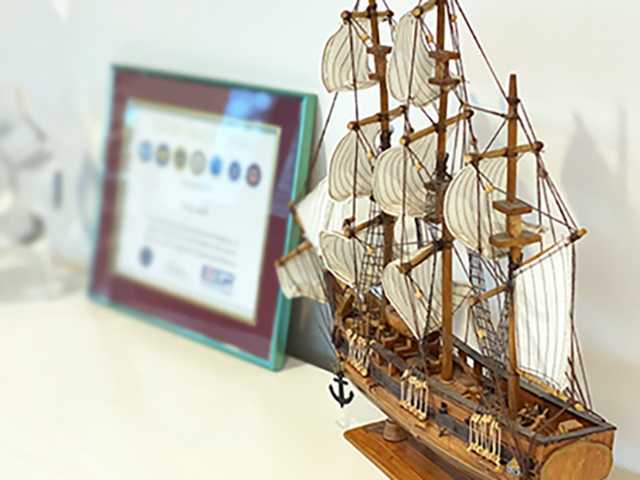 Model ship displayed alongside of various awards