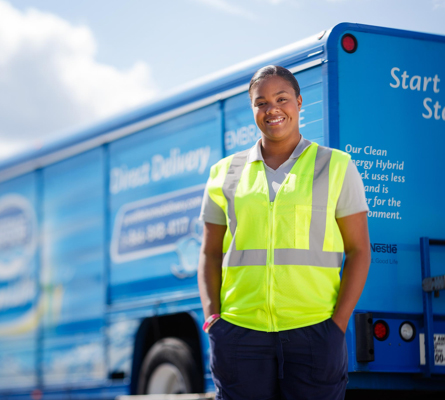 Nestle Waters brand photo - Water delivery driver standing in front of her truck