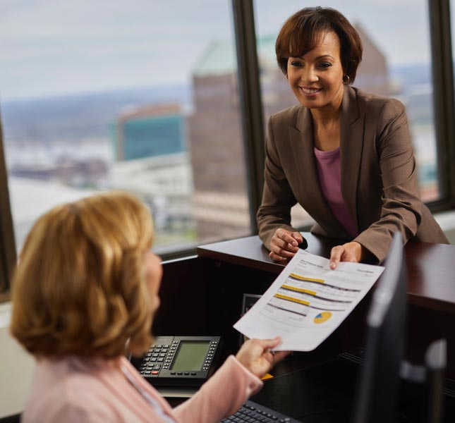 A financial advisor handing papers to an associate.