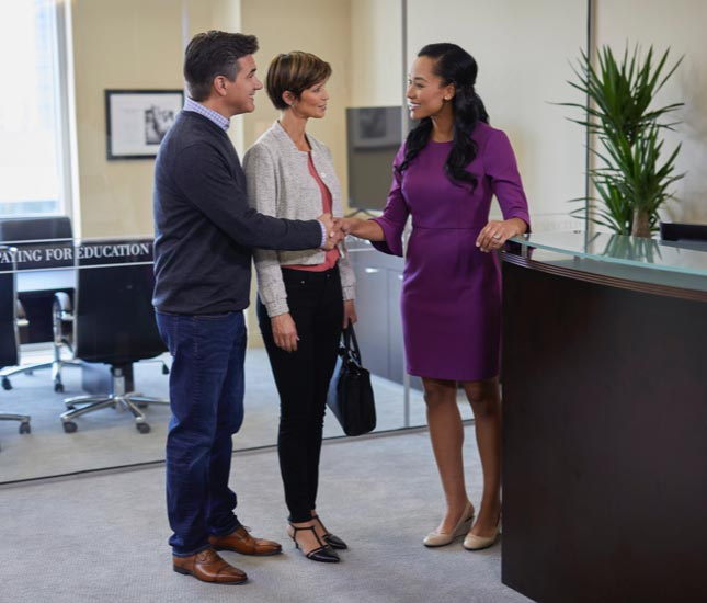 A couple standing at a desk shake hands with another woman.