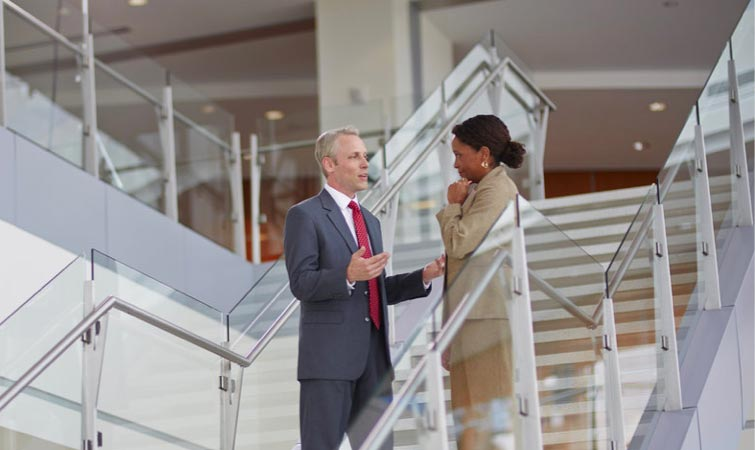 A man and woman having a discussion while standing on the landing of a flight of stairs.