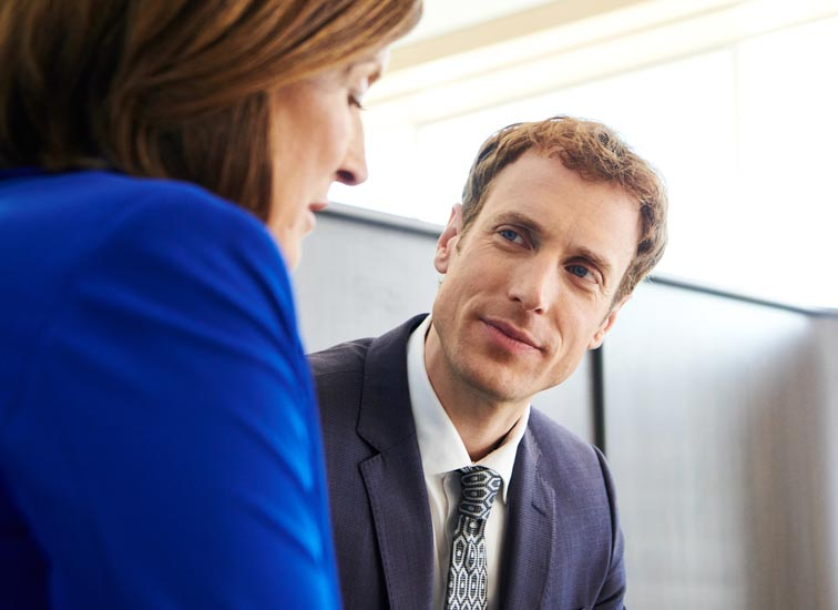 A man having a discussion with a woman in an office.