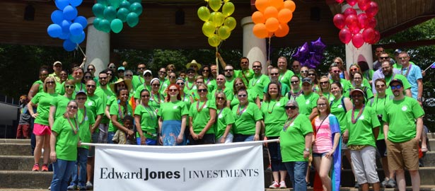 A large group of associates in green t-shirts stand behind an Edward Jones Investment banner.