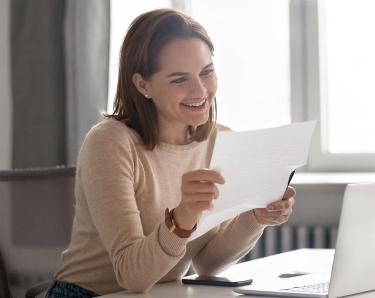 A smiling woman looking at paperwork at her desk.