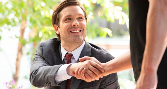 A smiling man handshake with other person