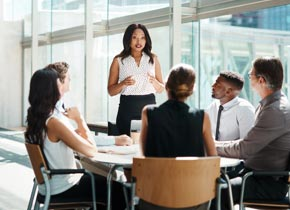 Professional group in a meeting setting with female speaker standing