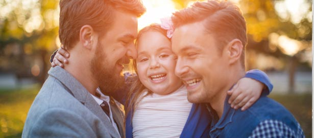 Two gay men hugging their young daughter.