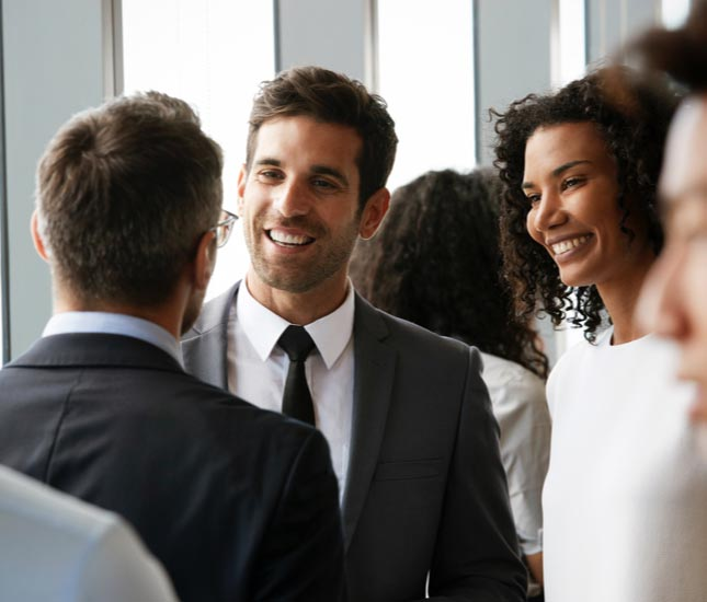 Two college graduates smiling and talking to a man