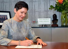 Penny Pennington, Managing Partner, signing a document while sitting at a desk.