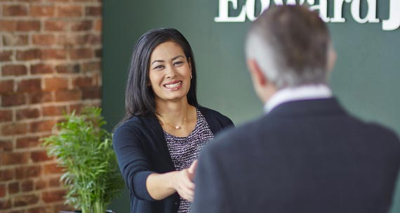 A smiling woman handshake with other person
