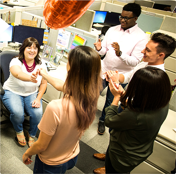 A group of male and female employees celebrating in an office cubicle, with a red balloon.
