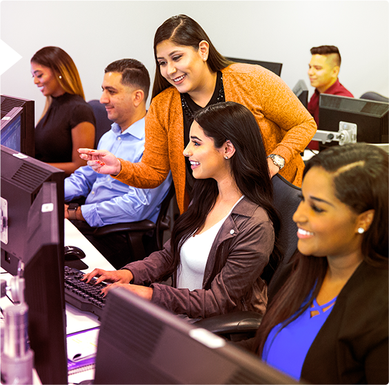 A group of male and female employees seated at computer desks in a classroom setting, looking at their own monitors.